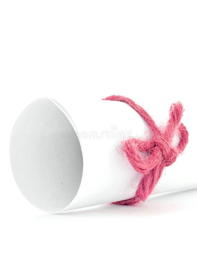 Handmade czerwony sznura guzek wiązał na białego papieru ślimacznicie odizolowywającej fotografia royalty free