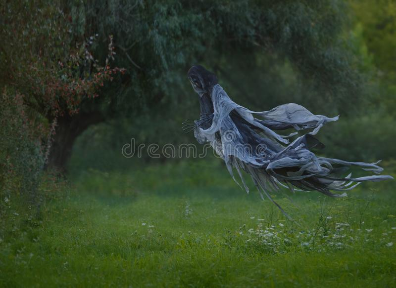 Handmade Death flies through the air with a wavy mantle into the forest above the lawn with green grass. autumn summer. Warm landscape. art photo. Halloween stock photography