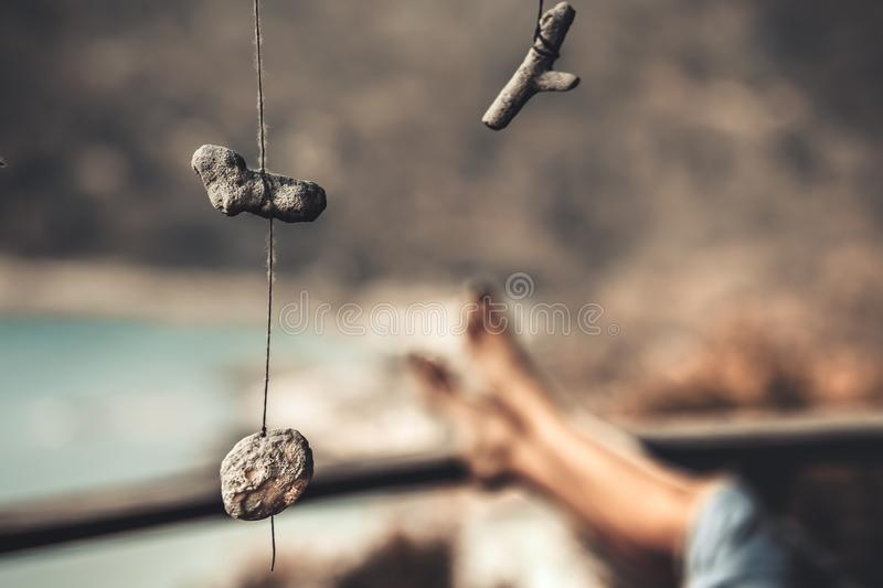Handmade decoration amulet and young woman legs. And Coastal Bottle Beach on Phangan Island Thailand Blurred Background Nature Landscape. Seaside Tourism Hotel royalty free stock photography