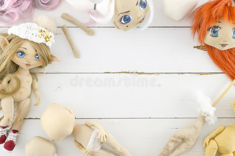 Handmade doll, needlework on a wooden white background. Frame with materials for sewing dolls royalty free stock photo