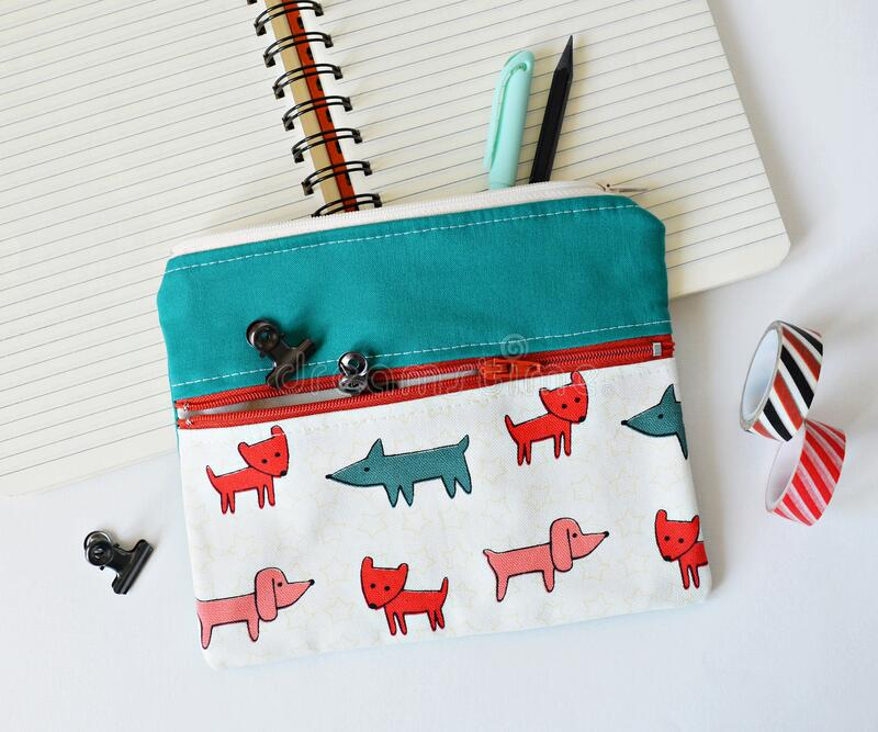 Double pocket pouch with dogs, clips, pencils, notebook and washi tape over white royalty free stock photos