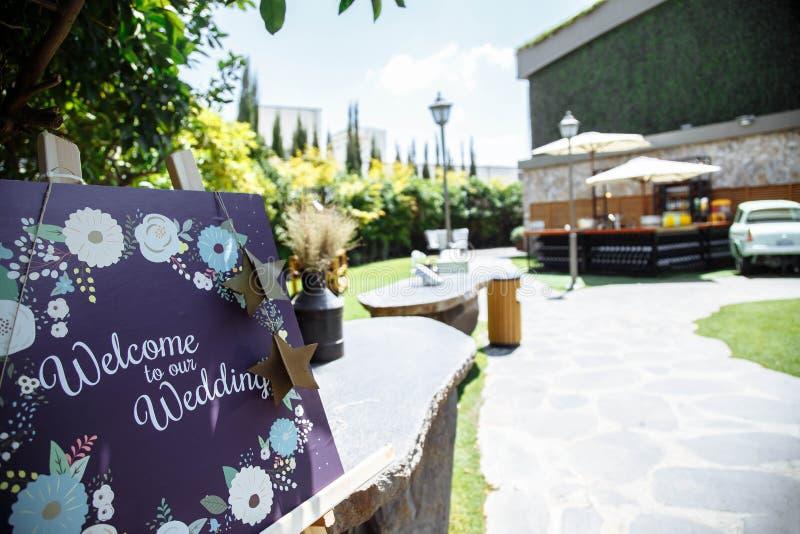 Handmade drewniana deska z znakiem powitalnym na nim dekorował z kwiatami plenerowymi zdjęcie royalty free