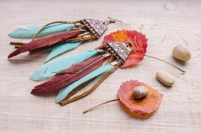 Handmade earrings with author`s ceramics and colored feathers. stock images