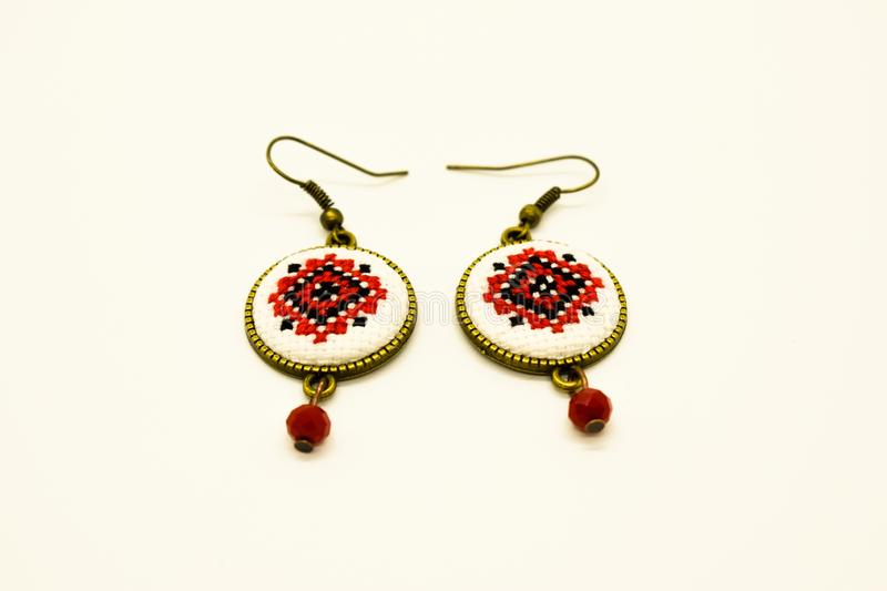 Handmade earrings with red and black romanian traditional model. Isolated on white. Handmade earrings with black and red romanian traditional model. Isolated on royalty free stock photography