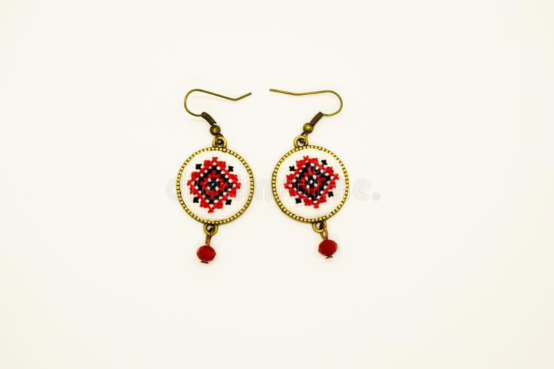 Handmade earrings with red and black romanian traditional model. Isolated on white. Handmade earrings with black and red romanian traditional model. Isolated on stock photos