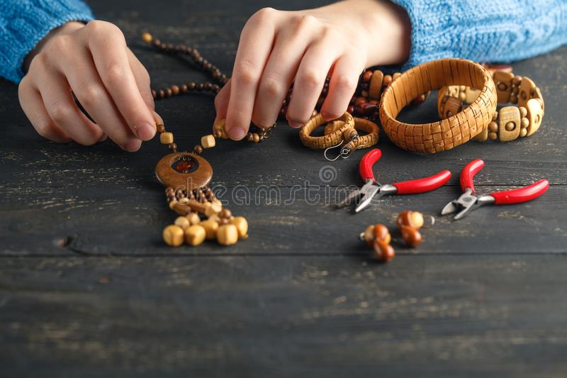 Handmade earrings making, home workshop. Woman artisan create tassel jewelry. Art, hobby, handicraft concept stock image