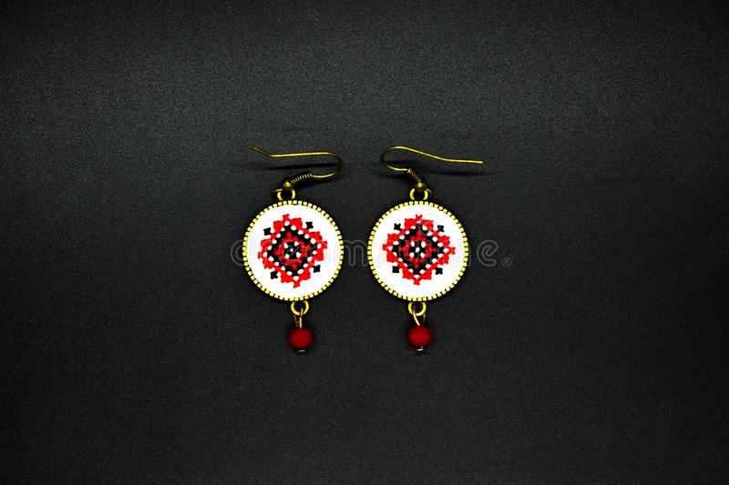 Handmade earrings with red and black romanian traditional model. Isolated on black. Handmade earrings with black and red romanian traditional model. Isolated on stock photo