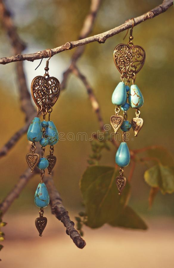 Handmade. Earrings with stones and golden hearts on the tree branch royalty free stock images