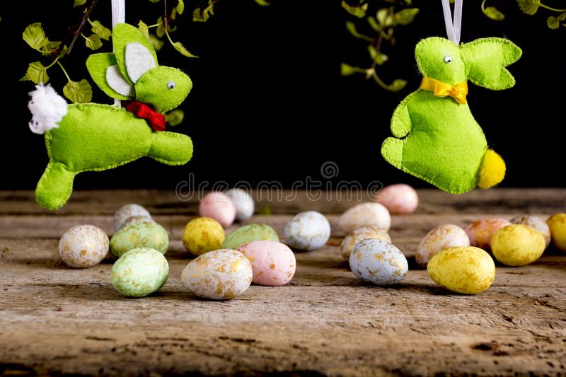 Handmade easter rabbits and eggs on wooden table. Black background. royalty free stock image