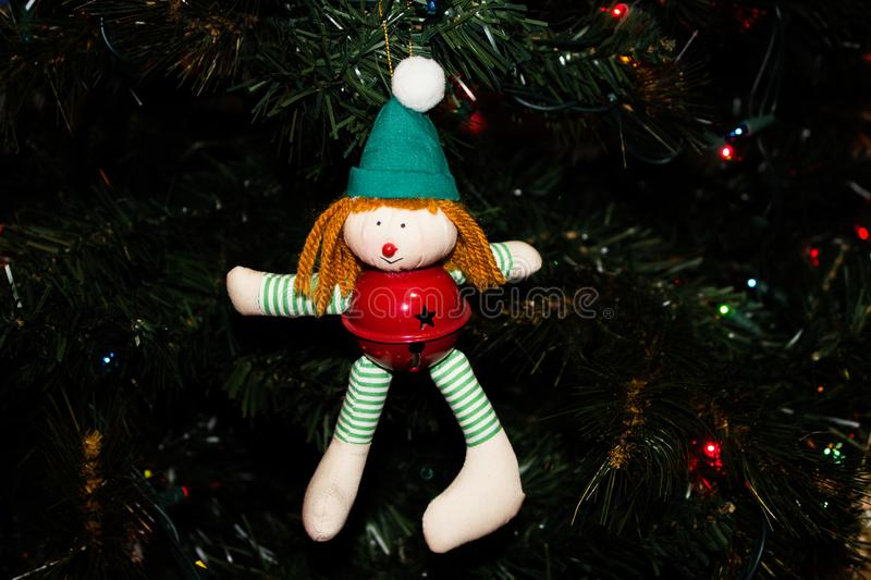 Handmade Elf Ornament with a Red Jingle Bell on a Christmas Tree stock images