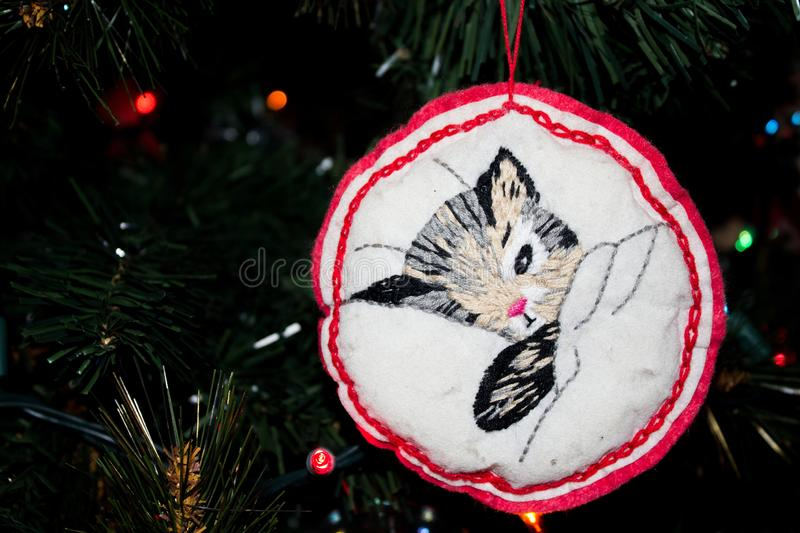Handmade Embroidered Christmas Ornament of a Kitty Cat on a Christmas Tree. Handmade Embroidered Christmas Ornament of a Kitty Cat hanging on a Christmas Tree stock image