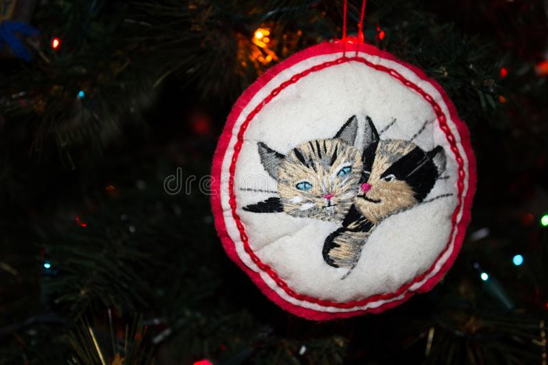 Handmade Embroidered Christmas Ornament of Two Kitty Cats on a Christmas Tree. Handmade Embroidered Christmas Ornament of Two Kitty Cats hanging on a Christmas royalty free stock photo