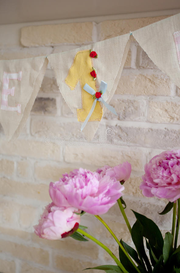 Handmade fabric garland with number one and bouquet of peonies. For child's birthday party stock photography