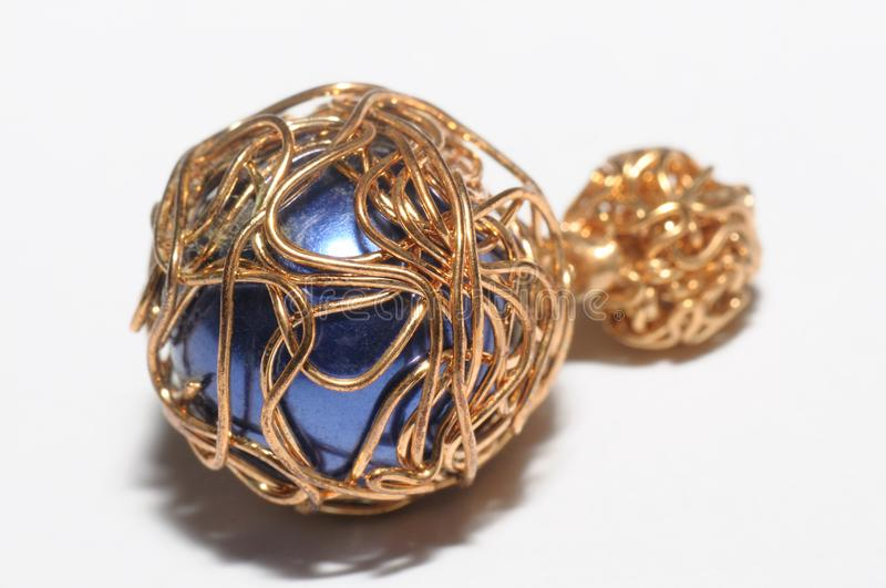 A handmade fake blue sapphire wrapped by metal wires stock photography