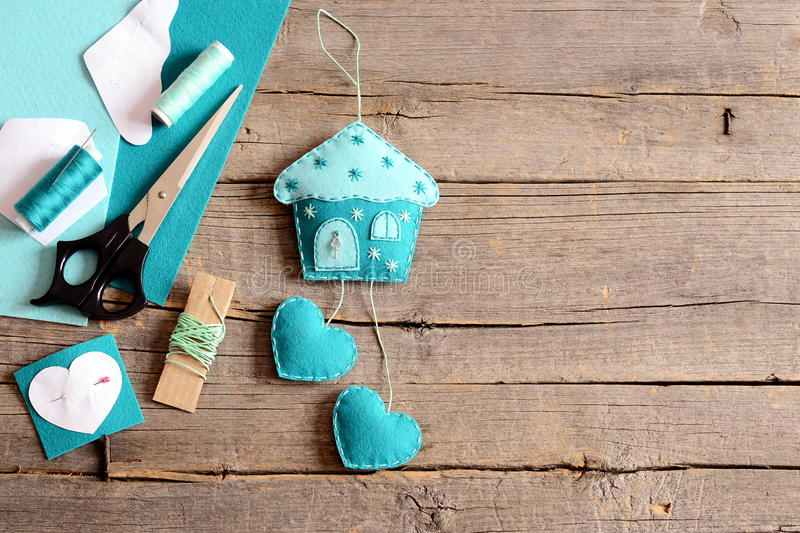 Handmade felt house with hearts ornament, tools and materials for hand making felt crafts, paper templates on wooden background stock image
