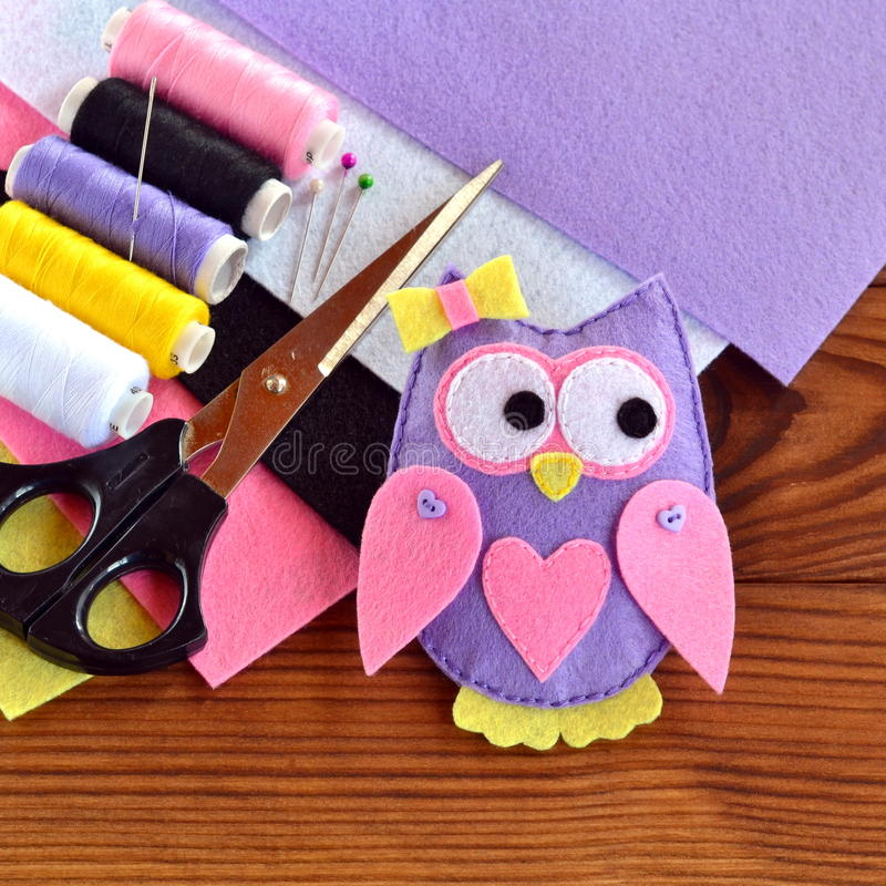 Handmade felt owl toy, felt sheets, scissors, thread, pins, needle on a brown wooden background. Sewing concept. Sewing toy. Owl toy. Toy ornament. Kids crafts royalty free stock photos