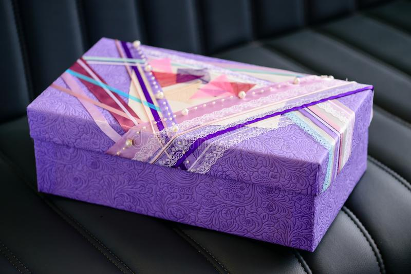 Handmade gift box wrapped with purple paper and decorated with w royalty free stock image