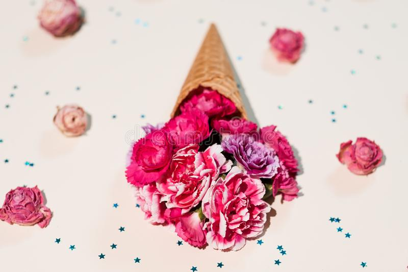 Handmade gift floral ice cream waffle cone star. Handmade gift. Abstract floral ice cream with carnation flowers in waffle cone on star pattern white background royalty free stock photo
