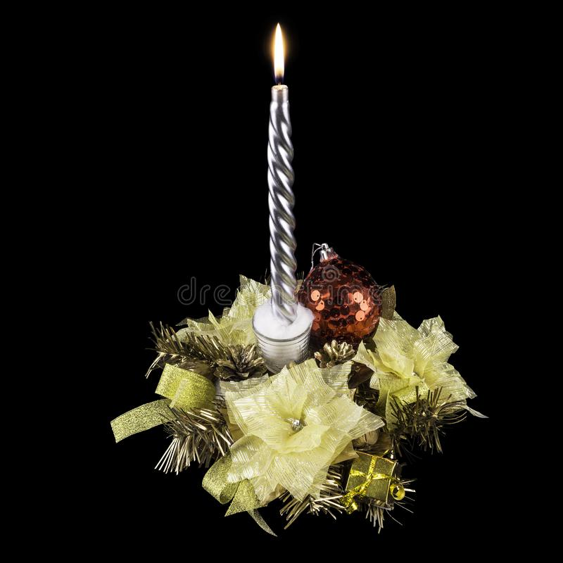 Handmade golden holiday decoration with decorative flowers, a red ball, branches of a Christmas tree and a burning candle, on a. Black background stock photos
