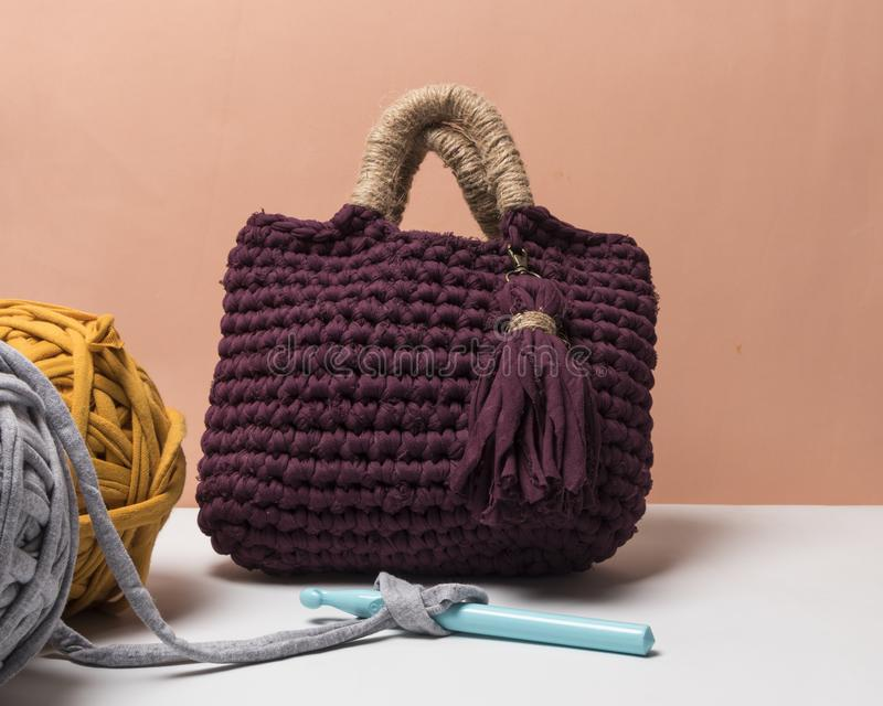 Handmade dark red and beige bag made with zpagetti yarn next to colored cloth balls royalty free stock photo