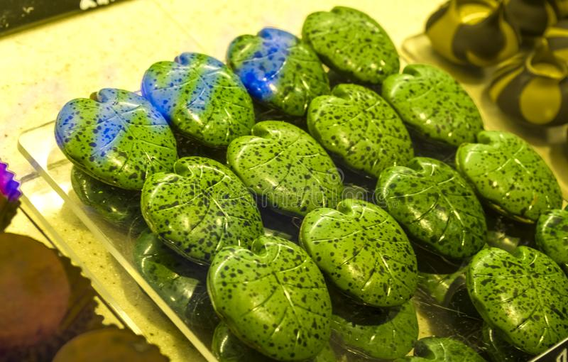 Handmade green candies in the form of monstera leafs on a show-window in shop. Tasty sweets. Supermarket, cafe. Unusual form. Handmade green candies in the form royalty free stock photography