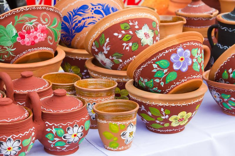 Handmade and handpainted ceramic clay pots, bowls and plates with floral and abstract pattern in the sunshine. Many handmade and handpainted ceramic clay pots stock images