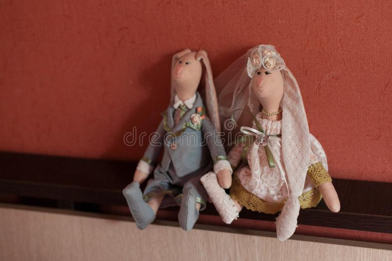 Handmade Hare Toys. Toys hares in dresses of the bride and groom are sitting on a wooden shelf on the background of the red wall stock image