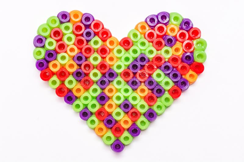 Handmade heart of plastic beads as a background royalty free stock image