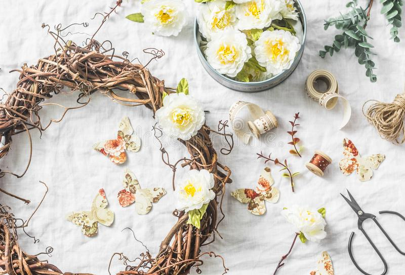 Handmade home interior decoration grapevine wreath with paper flowers and butterflies on a light background, top view. Flat lay stock photography