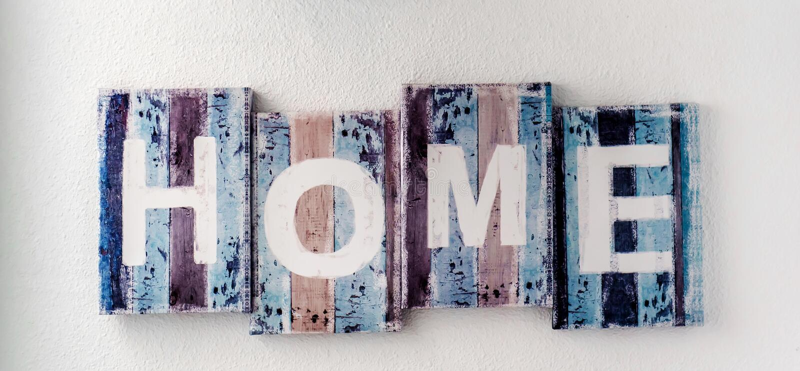 Handmade HOME sign. Wooden colorful planks over white wall background. Rustic decor