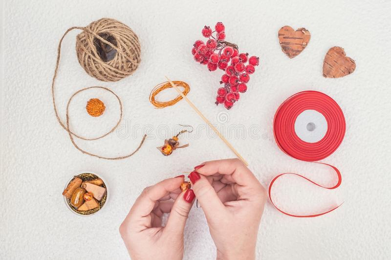 Handmade Jewelry, DIY flat lay in red and brown. Jewelry designer workplace. Woman hands making handmade earrings with amber. royalty free stock image