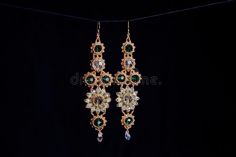 Handmade jewelry made of beads in macro. earrings from white beads. earrings from stones stock photography