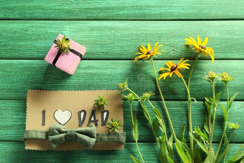 Handmade karta z zwrotem KOCHAM taty, prezenta pudełka i kwiatów na koloru drewnianym tle, Ojca dnia ?wi?towanie zdjęcia royalty free
