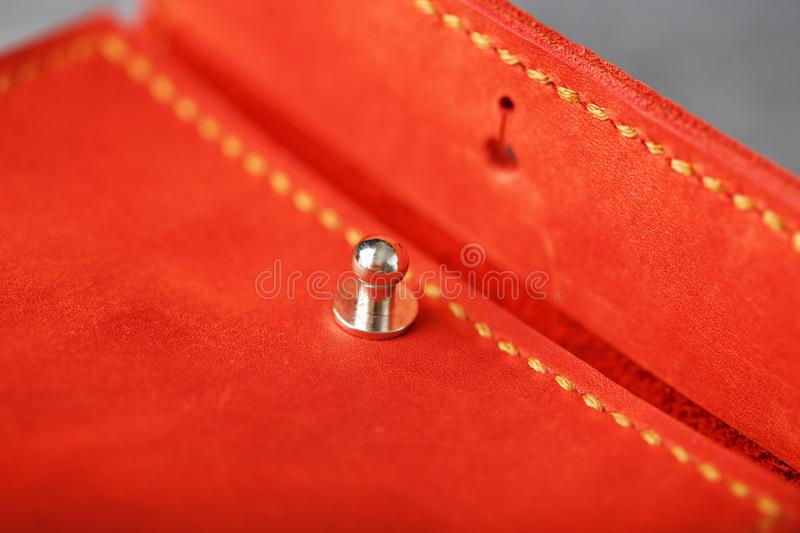 Handmade key holder made of genuine red leather on a dark background. Close-up stock photo