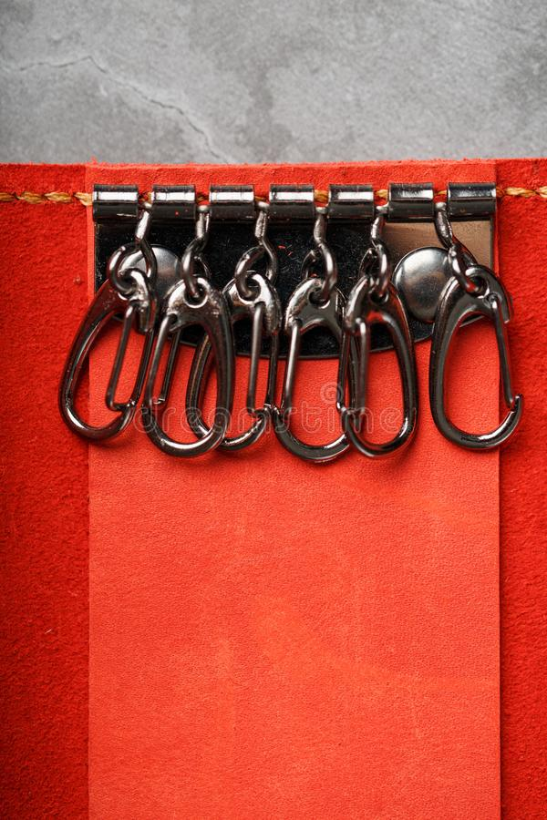 Handmade key holder made of genuine red leather on a dark background. Close-up royalty free stock images