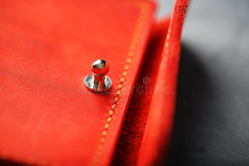 Handmade key holder made of genuine red leather on a dark background. Close-up stock images