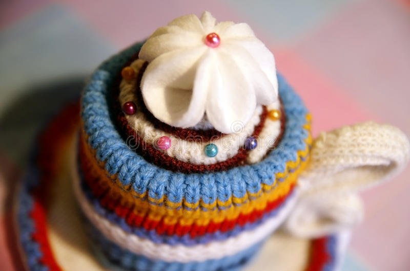 Handmade knitted cup of tea stock photos