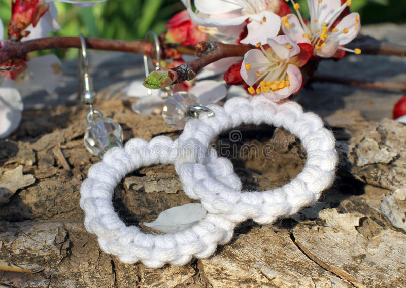 Handmade knitted round earrings on the nature background stock images