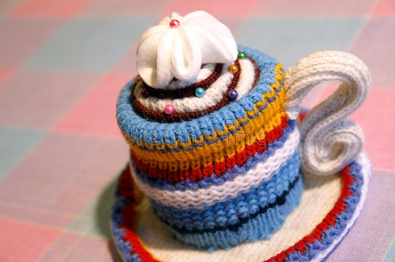 Handmade knitted striped cup of tea royalty free stock images
