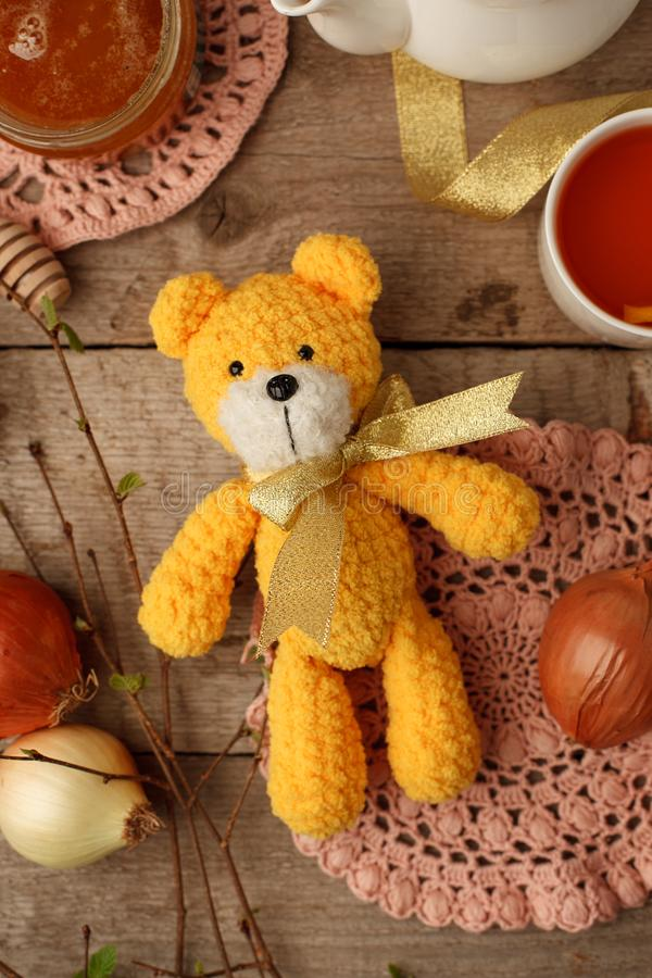 Handmade knitted toy, yellow crocheting funny bear on vintage wooden background. Adorable crochet baby toy stock images