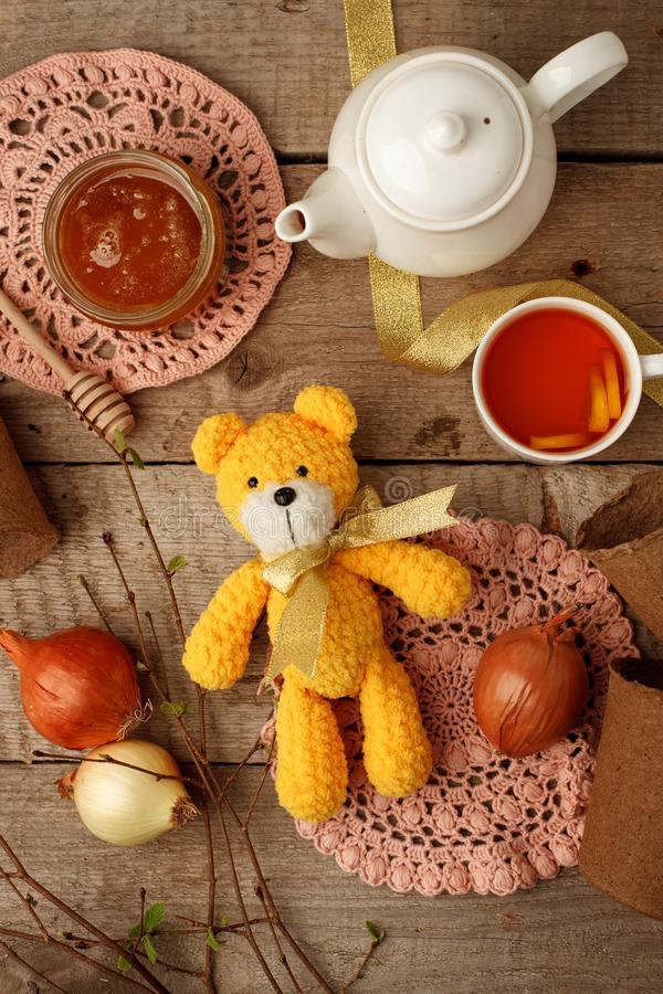 Handmade knitted toy, yellow crocheting funny bear on vintage wooden background. Adorable crochet baby toy stock photos
