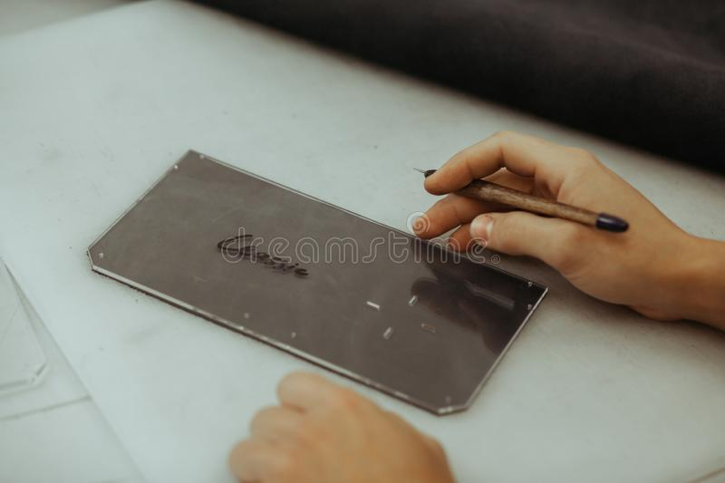 Handmade leather artisan making craft wallet using piece of natural leather on his working place with tools, close up. Photo of his hands. Leather craft stock image