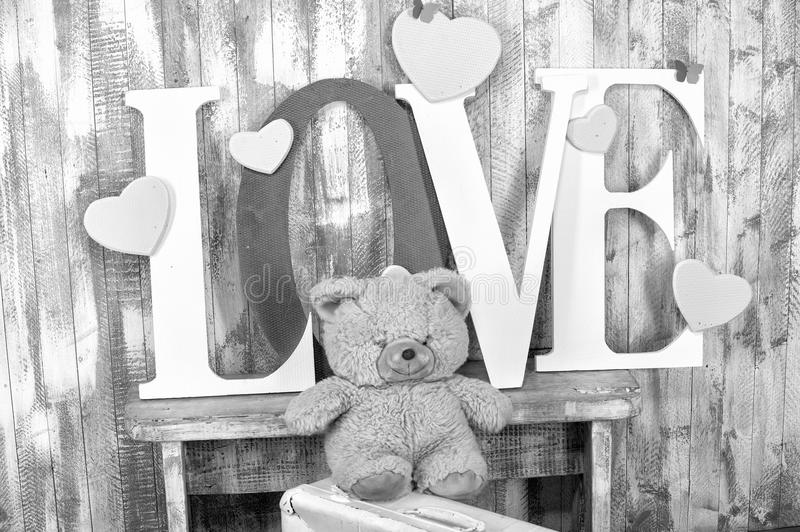 Love text with bear hearts and butterfly. Handmade letters with love word text red and white color near bear toy hearts and butterfly on wooden wall background royalty free stock photo