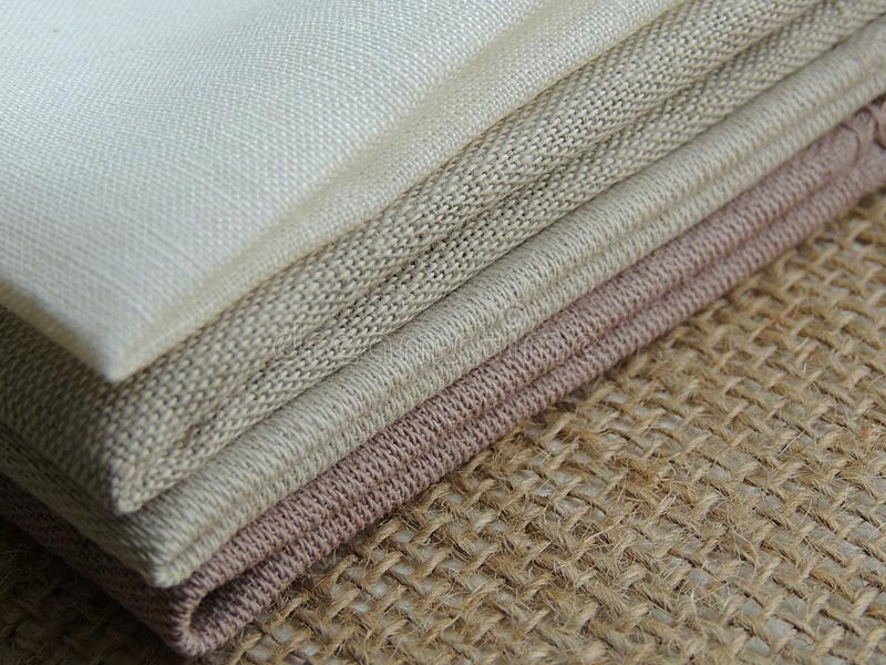 Handmade linen cotton napkins, kitchen towels on burlap background. royalty free stock photos