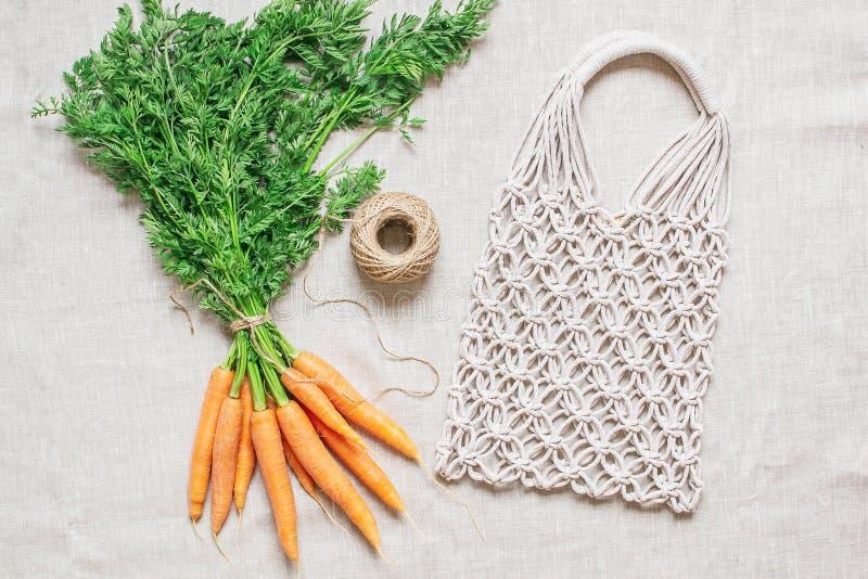 Handmade makramy torba z świeżymi marchewkami na bieliźnianym tle zdjęcie stock