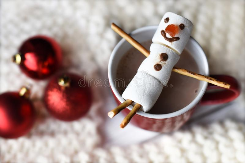 A handmade marshmallow snowman on a red cup with cocoa royalty free stock photography