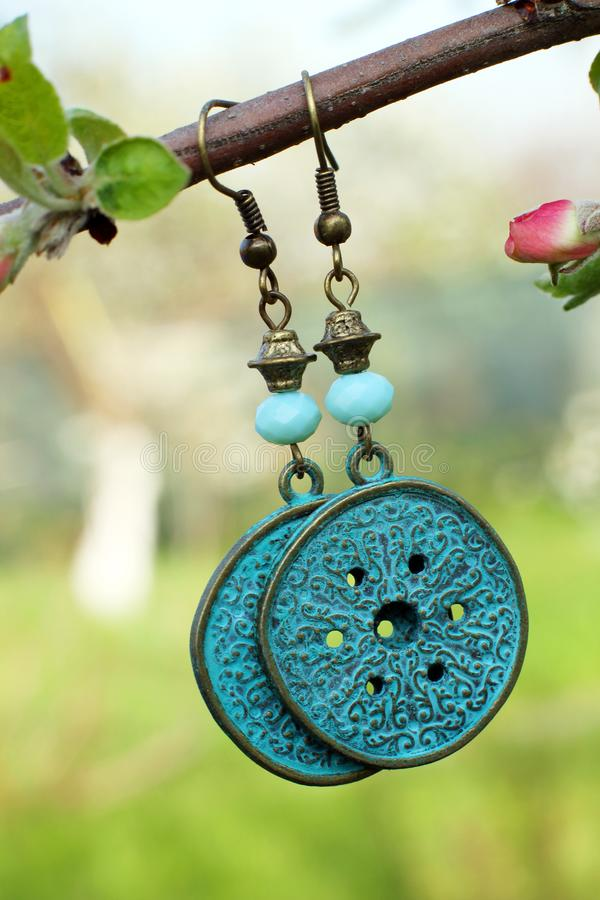 Handmade metal earrings on the nature background stock photography