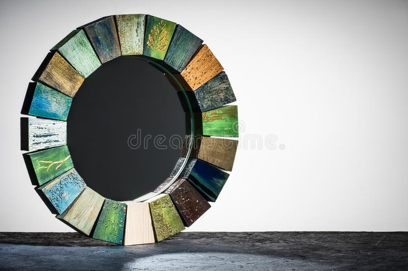 Handmade mirror in a wooden toned frame texture cracked paint. And without reflection black glass rustic style on a gray stone background in front of a light stock photos