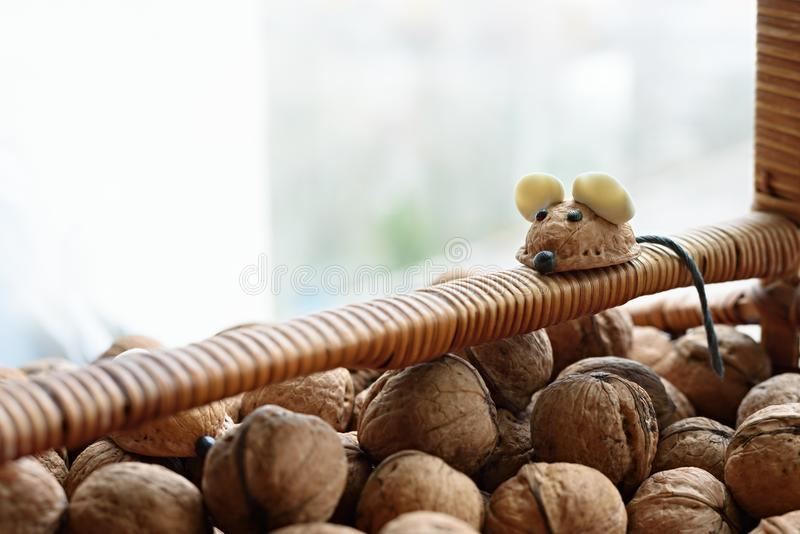 Handmade mouse made from walnut shell on the handle of a basket with nuts royalty free stock image