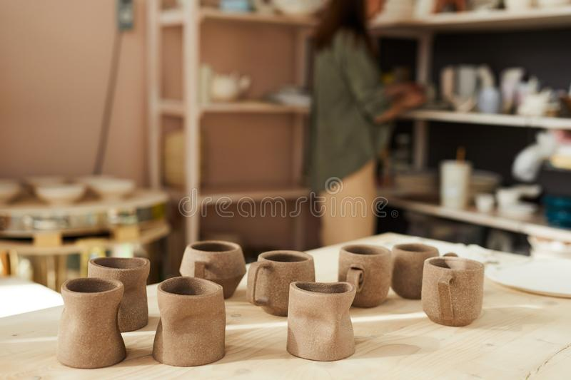 Handmade Mugs in Pottery Shop. Background image of clay mugs on wooden table table in traditional pottery shop, copy space stock images
